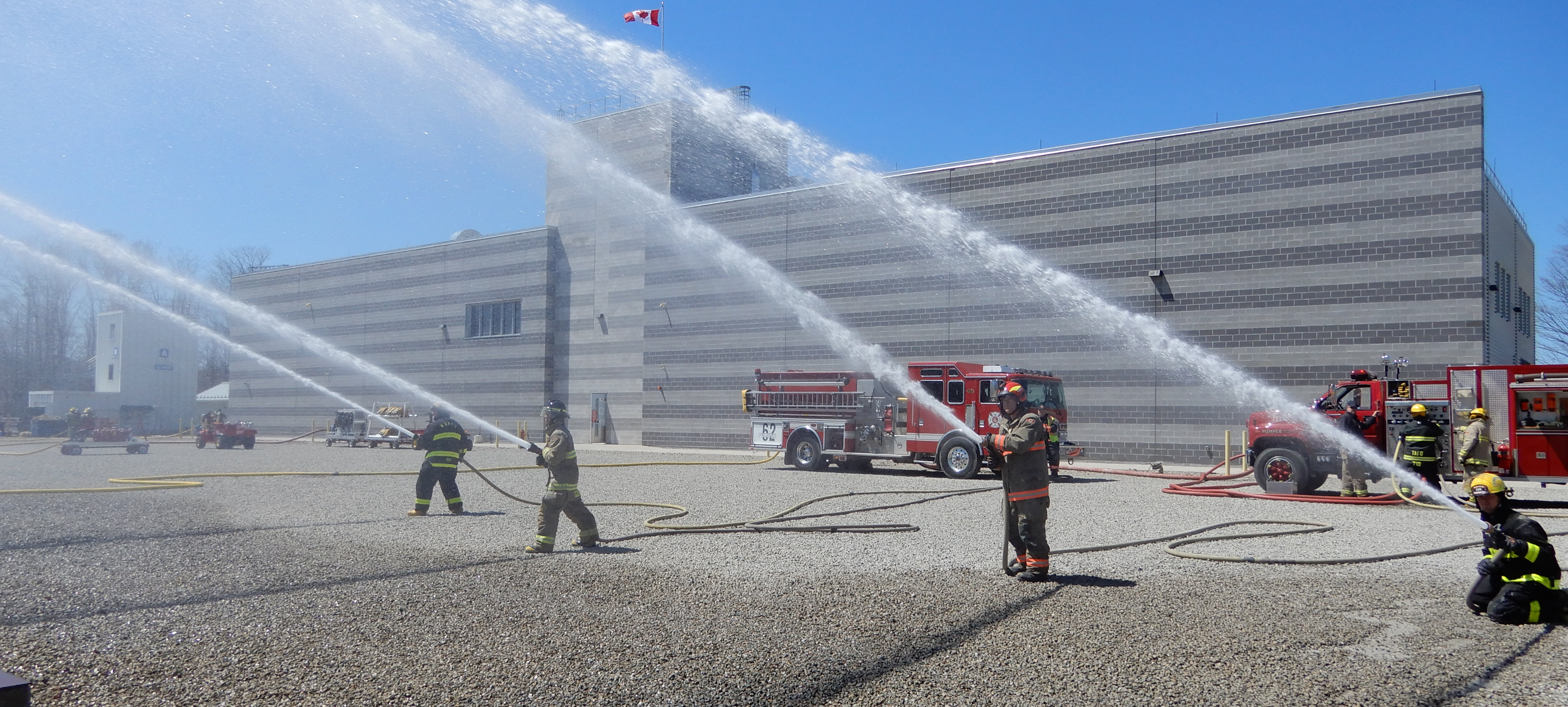 Firefighters spray hoses during training