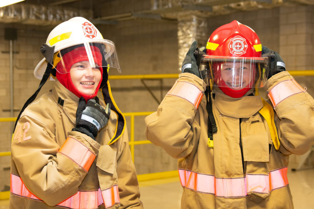 Youth try on firefighter gear at Take Our Kids to Work Day