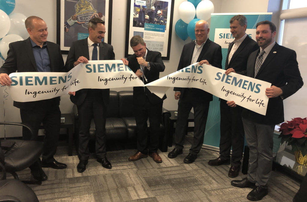 Dignitaries cut ribbon at Siemens office